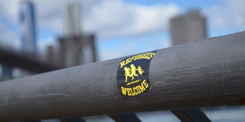 "PHOTO: A ""refugees welcome"" sticker in New York - via Pixabay (CC0)."