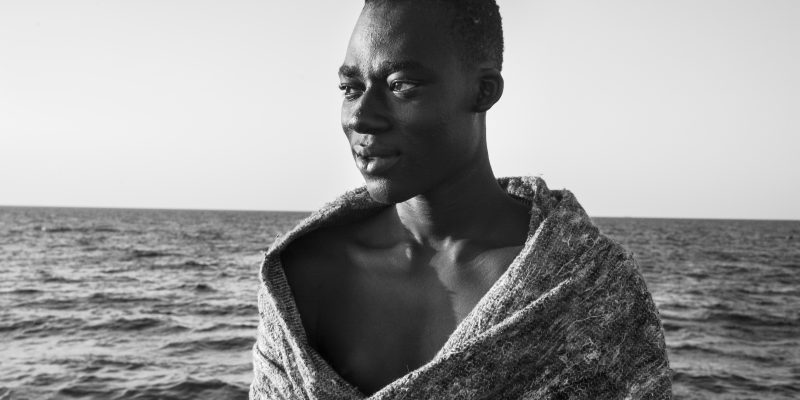 Malick, from Gambia, looks at the sea from the rescue vessel Iuventa, seven hours after departing from Libya in a rubber boat with 120 others. (Photo: César Dezfuli)