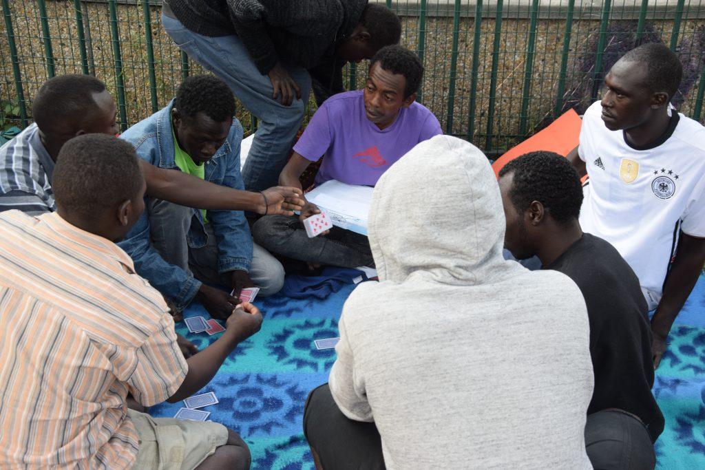 Migranti giocano a carte all'accampamento informale di Porte de la Chapelle, aspettando l'ora conclusiva del digiuno per il Ramadan (foto: Veronica Di Benedetto Montaccini)