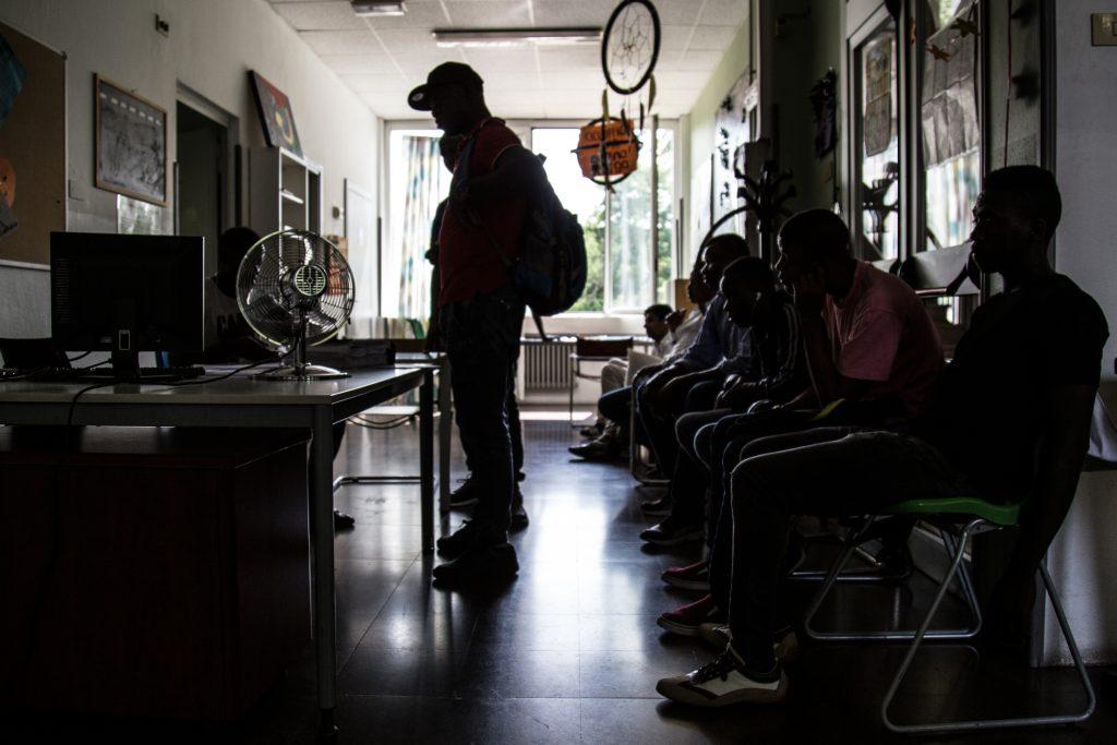 Richiedenti asilo provenienti da Africa e Asia attendono il loro turno per parlare con uno dei volontari del centro Naga-Har di Milano e preparare la propria audizione davanti alla Commissione territoriale. (foto: Matteo Congregalli)