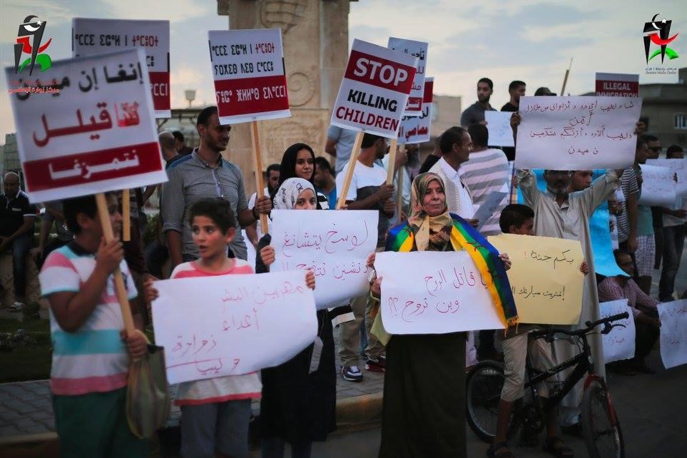 """Manifestazione della società civile di Zuwara il 28 agosto 2015 contro i trafficanti. I cartelli sono in lingua inglese, araba e tamazigt. Uno di questi dice: """"Omicida di anime, dove vai?"""" (Foto: Zuwara Media Center)"""