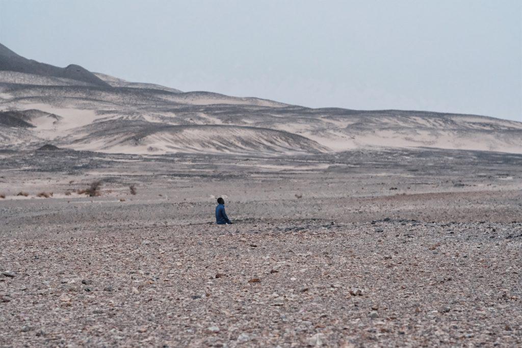 Un autista prega vicino alle miniere d'oro di Aouzouger, lungo la rotta sahariana verso la Libia (foto: Giacomo Zandonini)