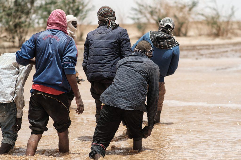 Migranti che attraversano un corso d'acqua dopo una tempesta, sulla rotta sahariana verso la Libia (foto: Giacomo Zandonini)
