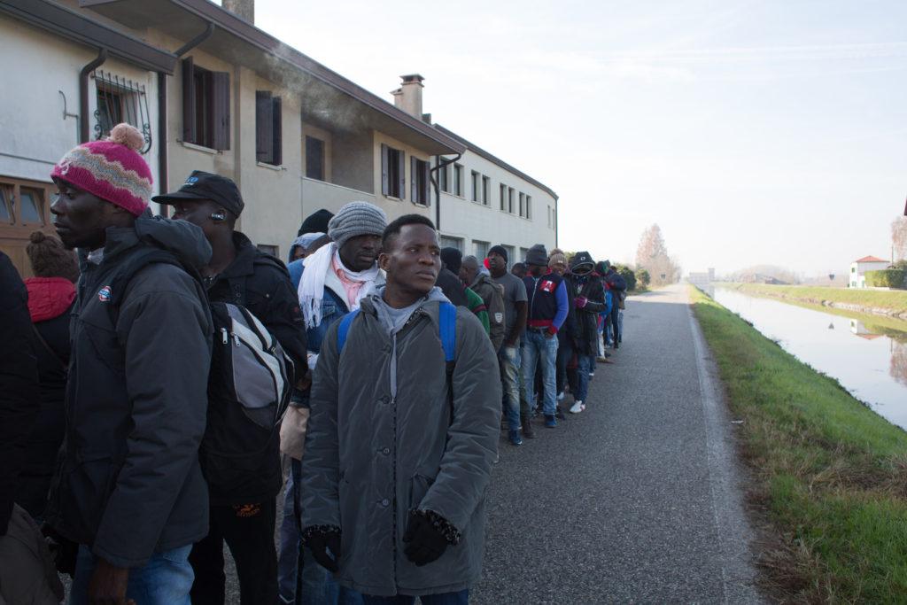 Strada statale, Veneto, 2017. Un momento di pausa durante la marcia dei 54 migranti (foto: Arianna Pagani)