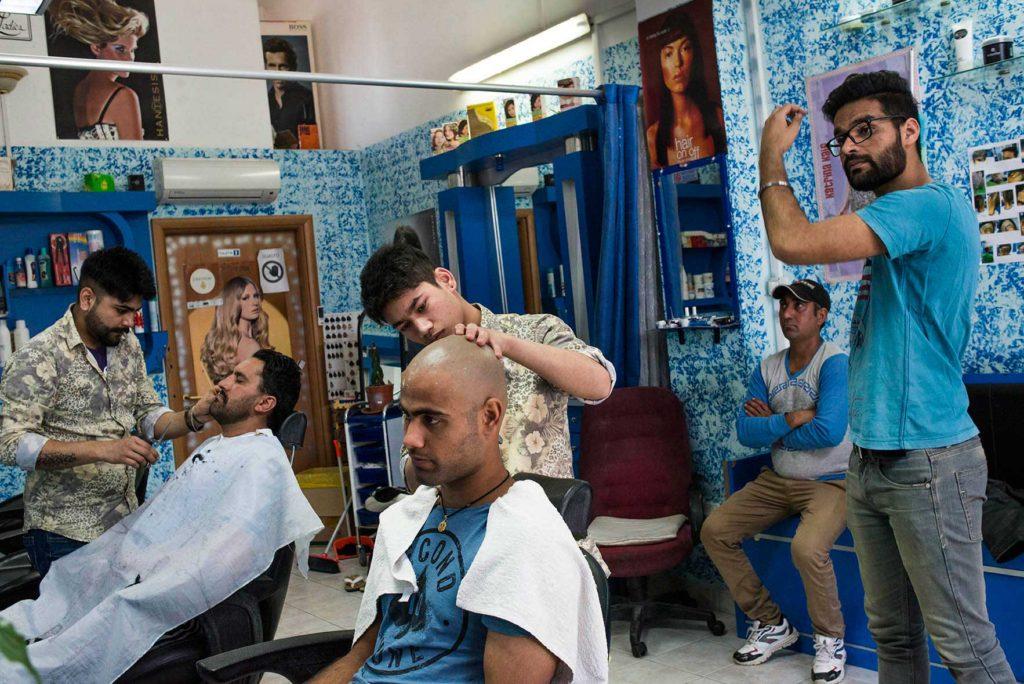 """Pontinia (Lt) - 2016. Keshav taglia i capelli di Charanjeet. Nella comunità Sikh i barbieri hanno un ruolo particolare in quanto, secondo la loro religione, un credente non dovrebbe mai tagliarsi i capelli. Ad ogni modo è concesso e tollerato essere credenti """"alla moda"""" (foto: Marco Valle)"""