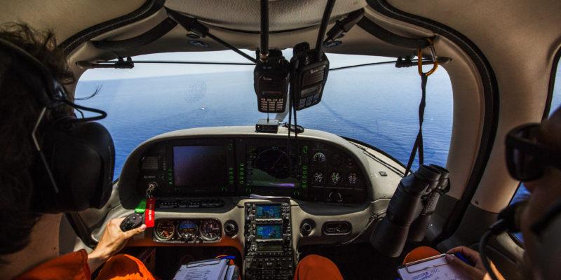 All'interno della cockpit di Moonbird, osservando alcuni target in mare. Mark, un pilota svizzero di 31 anni della Humanitarian Pilot Initiative, e Tamino Böhm, l'operatore di volo, sono volontari che credono nella necessità di fermare le morti di massa in mare (foto: Alessio Mamo)