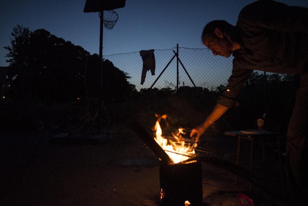 S. cuoce la cena su un pentolino da campeggio accanto alla tenda in cui ora vive con la compagna (foto: Federica Mameli)