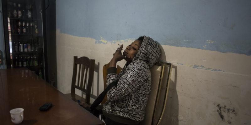 All'interno di una connection house di Destra Volturno, B. in un momento di pausa nel salone in cui i clienti sono soliti bere prima di consumare sesso nelle stanze adiacenti (foto: Federica Mameli)