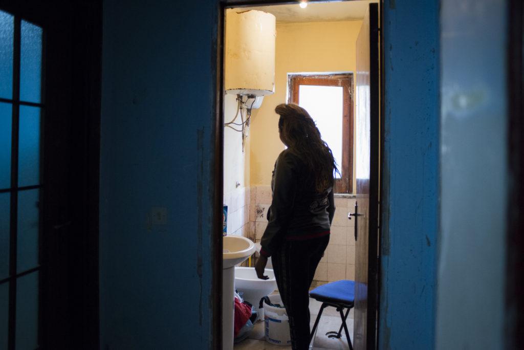 Una ragazza all'interno della connection house in cui vive e in cui è costretta a prostituirsi per saldare il debito contratto con la Madame (foto: Federica Mameli)