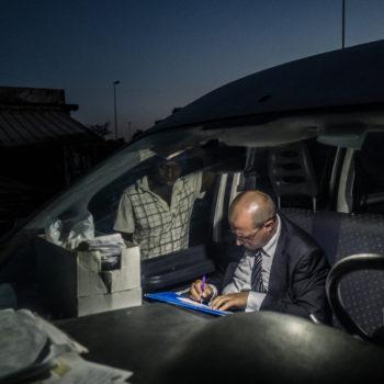 Massimo, volontario italiano, aiuta un residente della tendopoli nella compilazione della richiesta del permesso di soggiorno. San Ferdinando, 2017 (foto: Diego Fedele)