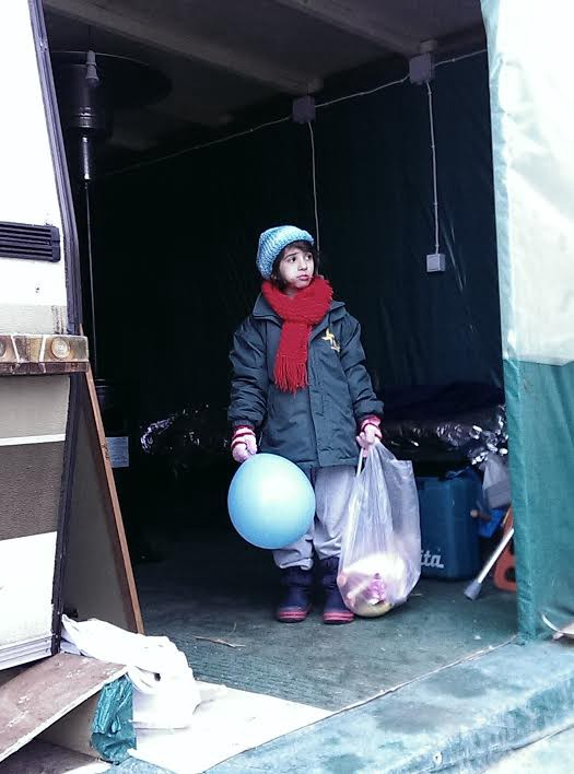 Skala Sikaminia: just arrived from Turkey, a child receives some gifts from the volunteer