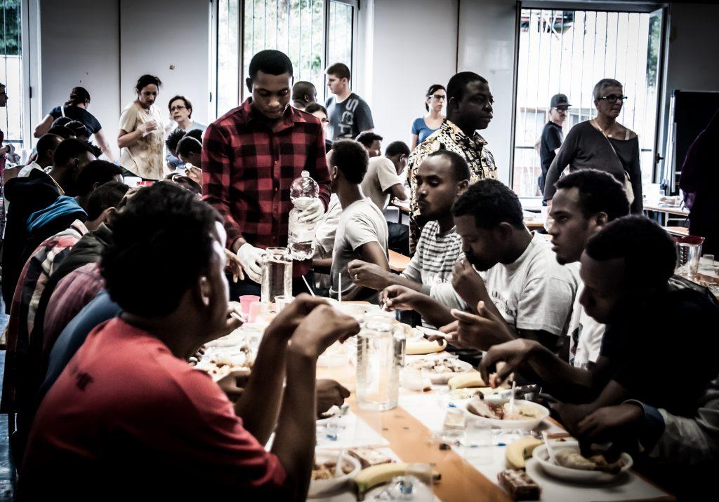 Didascalia Como. Migranti consumano il pasto distribuito dalla Caritas nella mensa allestita a S.Eusebio. (Foto: Emanuele Amighetti)
