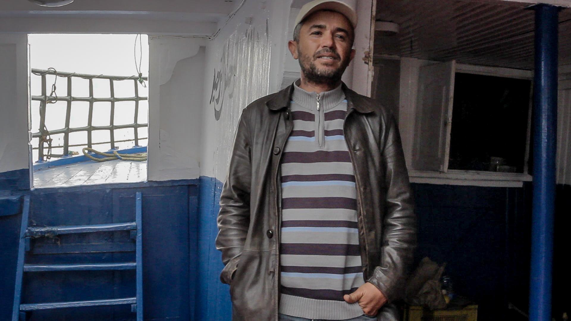 Anis Belhaj, pescatore di Zarzis e membro dell'associazione pescatori, sulla sua barca accanto al deposito viveri (foto: Giulia Bertoluzzi)