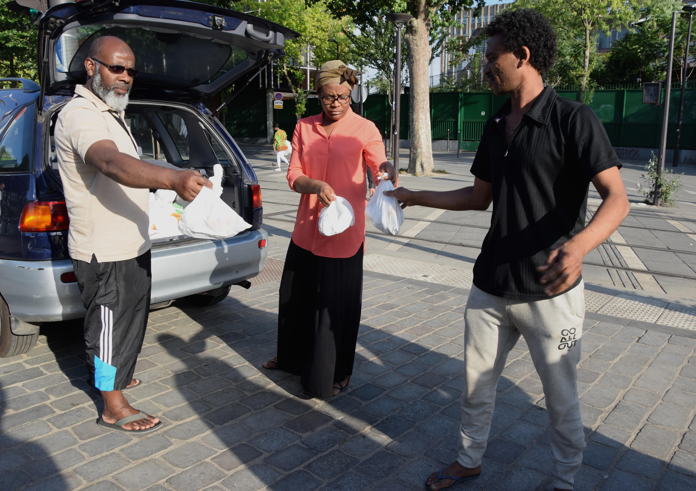 Volontari distribuiscono pacchetti di cibo all'accampamento informale di Porte de la Chapelle (foto: Veronica Di Benedetto Montaccini)