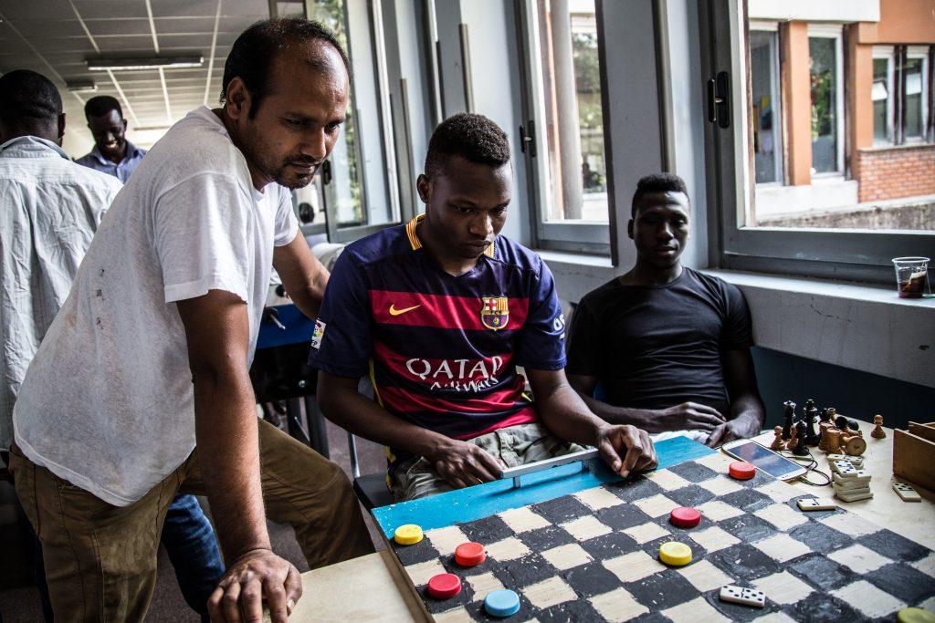 Alcuni richiedenti asilo giocano a dama al centro Naga-Har di Milano. La noia spesso riempie i giorni di chi attende un'audizione in Commissione territoriale (foto: Matteo Congregalli)