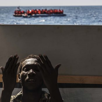 Safe aboard MSF's Dignity I sea rescue vessel this man prays as the rescue of others from a dingy continues behind him (photo: Anna Surinyach)