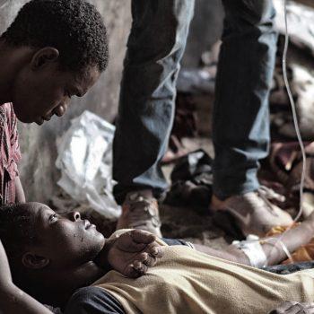 Sow Ammar, migrante guineano, assiste una giovane nigeriana disidrata dopo giorni nel Sahara (foto: Giacomo Zandonini)
