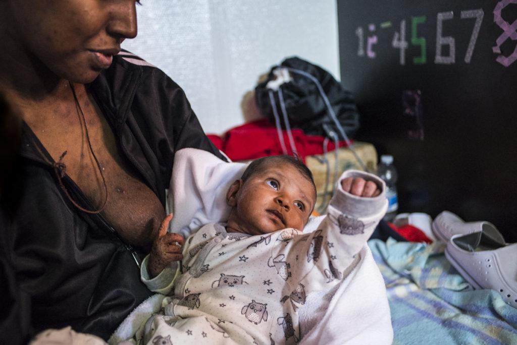 27 dicembre 2017. Mediterraneo centrale. Nello shelter dell'Aquarius, una giovane ragazza somala riposa e tiene in braccio la figlia di soli due mesi. Madre e neonata, nata in Libia in un centro di detenzione, hanno entrambe il corpo ricoperto di scabbia (foto: Federica Mameli/SOS Méditerranée)