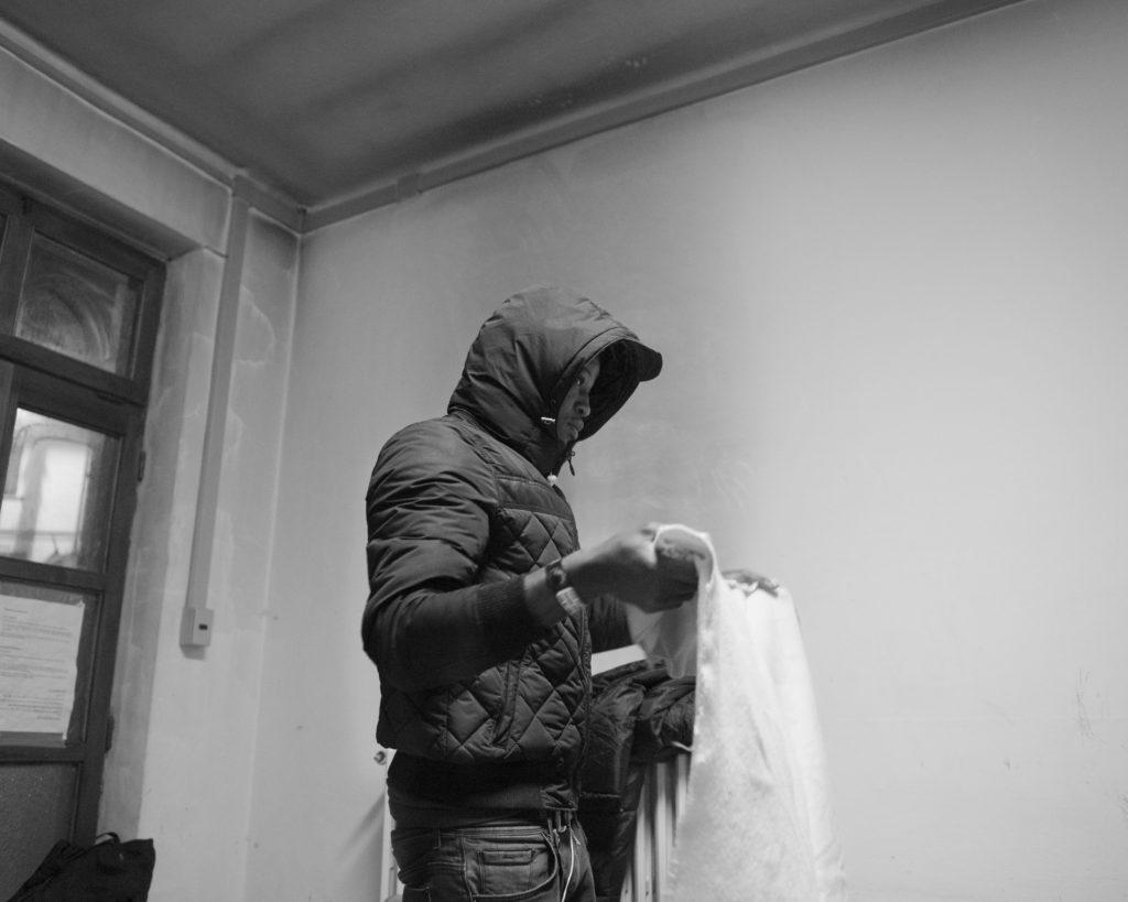 Un migrante si prepara il letto nel centro d'accoglienza di Bardonecchia (foto: Emanuele Amighetti)