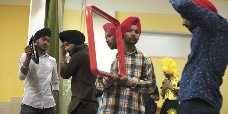 Pontinia (Lt) - 2015 - Parminder tiene lo specchio a un amico mentre indossa il turbante, uno dei simboli tradizionale del sikhismo (foto: Marco Valle)
