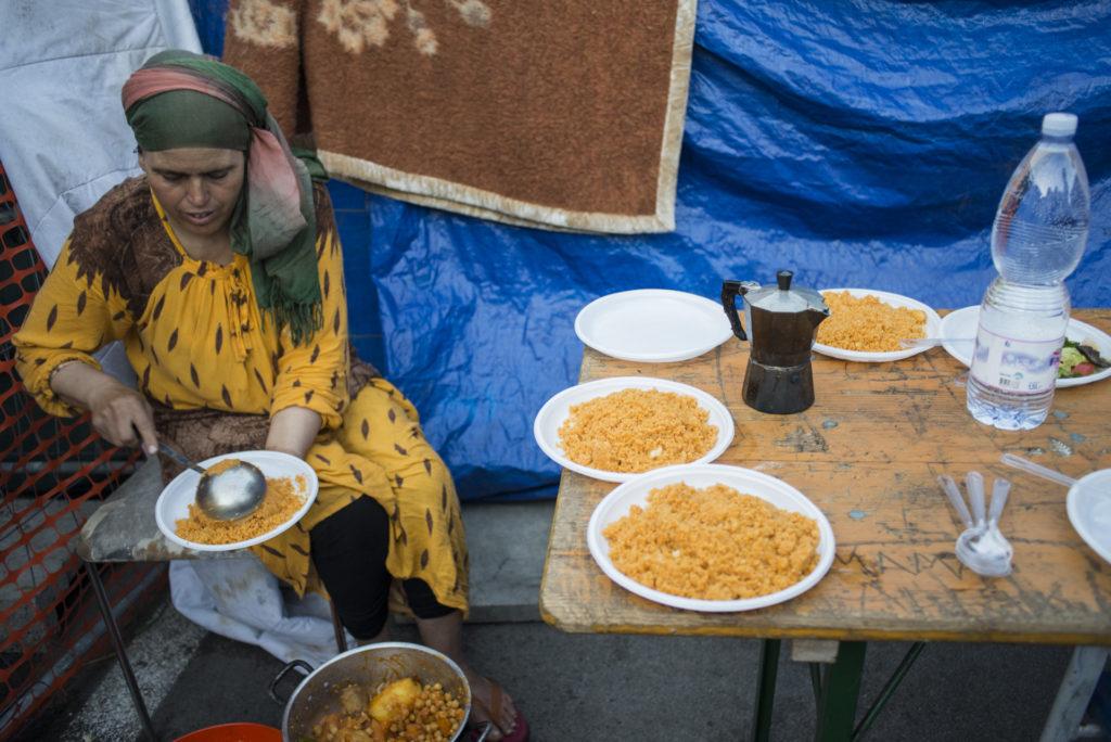 Rabia serve la cena per la sua famiglia sul selciato adiacente alla tenda in cui dorme insieme ai figli e al marito (foto: Federica Mameli)