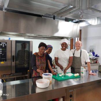 Nella cucina di casa Chiaravalle, Hortense Melingui (Camerun), Theresa Ajiri Ugbeta (Nigeria), Fatima Umbuya (Sierra Leone), e lo chef Fabio Viola (foto: Antonio Martella)
