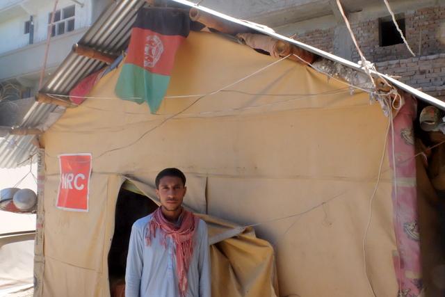 Hakim, 25 anni, di fronte alla tenda in cui vive con la sua famiglia di 8 persone, nella periferia di Jalalabad