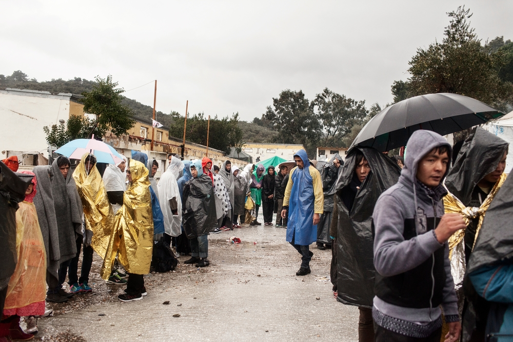 Refugees queue during a rain storm as they wait to be registered at the Moria Reception Centre in Lesbos, Greece